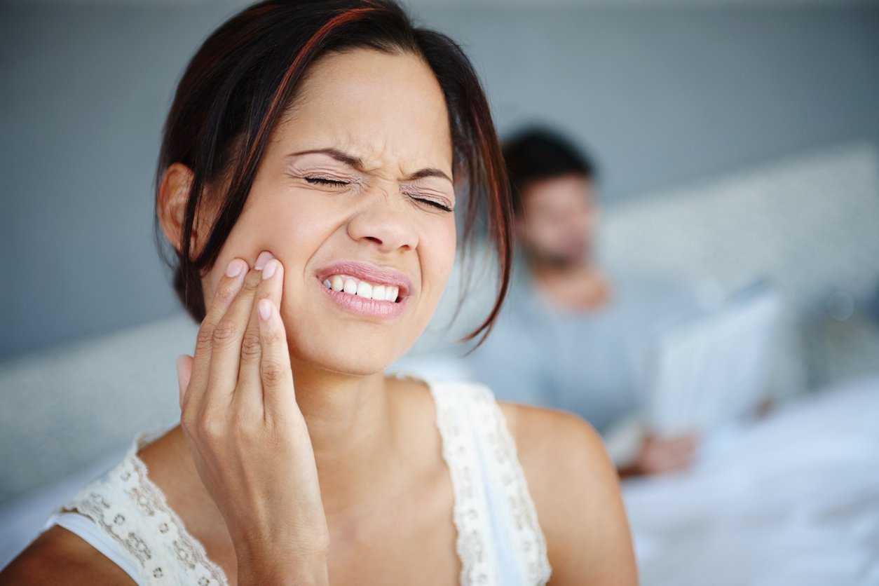 Shot of a woman sitting on the side of her bed with bad toothache with her boyfriend in the background